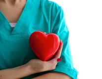 Young woman doctor holding a red heart, in office royalty free stock photography