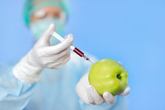 Young woman doctor injecting green apple Royalty Free Stock Images