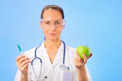 Young woman doctor injecting green apple Stock Image