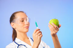 Young woman doctor injecting green apple Stock Photography