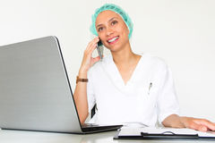 A young woman doctor With a laptop in her office  talking on the phone Royalty Free Stock Images
