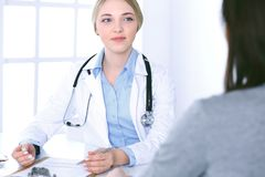 Young woman doctor and patient at medical examination at hospital office. Blue color blouse of therapist looks good. Young women doctor and patient at medical royalty free stock photos