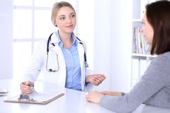 Young woman doctor and patient at medical examination at hospital office. Blue color blouse of therapist looks good. Young women doctor and patient at medical stock image