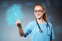 The young woman doctor pressing virtual buttons. Young woman doctor pressing virtual buttons Royalty Free Stock Image