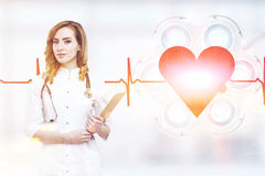 Young woman doctor. With red hair and a clipboard is standing in an operating theatre with a surgical lamp, a large red heart and a rhythm in the background Royalty Free Stock Photos