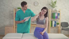Young woman at the doctor`s chiropractor osteopath complains of pain in the forearm stock footage