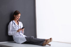 Young woman doctor sitting on the floor with your Royalty Free Stock Photography