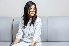 Young woman doctor sitting on the sofa. stock images