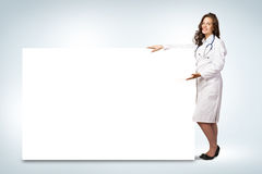 Young woman doctor standing near a blank banner Royalty Free Stock Photography