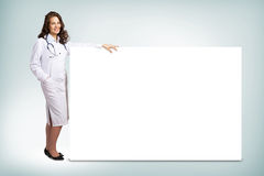 Young woman doctor standing near a blank banner Stock Photos