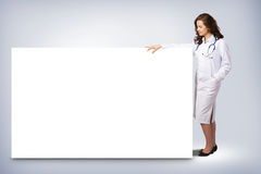 Young woman doctor standing near a blank banner Royalty Free Stock Photo