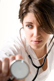 Young woman doctor with stethoscope. On white background. Focused on face Stock Photos