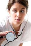 Young woman doctor with stethoscope. On white background. Focused on stethoscope Royalty Free Stock Images