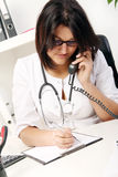 Young woman doctor talking by phone Royalty Free Stock Photography