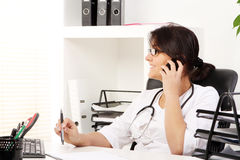 Young woman doctor talking by phone stock photography