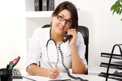 Young woman doctor talking by phone Stock Images