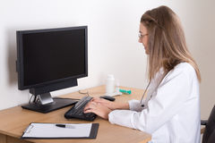 Young woman doctor using computer in office Royalty Free Stock Images
