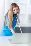 Young woman doctor in white coat at computer using Stock Photos