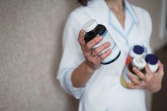 Young woman doctor in white medical robe holding in her hand the bottles of medication or vitamins. No face. Close up. royalty free stock image