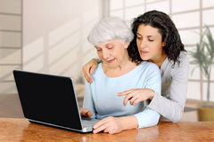 Young woman doctrine teaches daughter of an elderly woman laptop computer. Young women doctrine teaches daughter of an elderly women how to work using laptop stock images