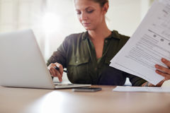 Young woman with documents working on laptop Stock Photography