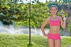 Young woman does dumbbell exercises in morning garden Stock Photo