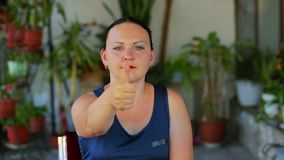 A young woman does an exercise with the eyes of a movement while looking at a finger and postponing it. The average plan stock footage