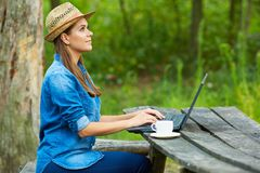 Young woman does homework with laptop. In garden Royalty Free Stock Photo