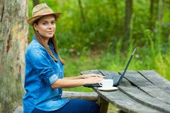 Young woman does homework with laptop. In garden Stock Image