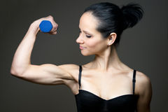 Young woman does sports with barbell Royalty Free Stock Image