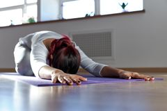 young woman does yoga exercises on a Mat lying face down with outstretched arms concert meditation yoga relaxation inner harmony. royalty free stock photography