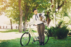 Young woman with dog and bicycle in the park Stock Photography