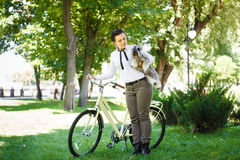 Young woman with dog and bicycle in the park Royalty Free Stock Photography