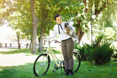 Young woman with dog and bicycle in the park Stock Image