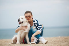 Young woman with a dog on a deserted beach Royalty Free Stock Image