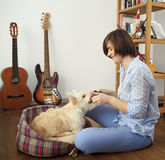 Young woman with a dog at home. Girl in blue shirt and trousers playing with white scotch terrier on the flour Stock Photography