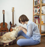 Young woman with a dog at home. Girl in blue shirt and trousers playing with white scotch terrier on the flour Stock Image