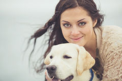 Young woman, dog labrador. Portrait of beautiful young woman playing with dog on the sea shore stock photo