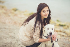 Young woman, dog labrador. Portrait of beautiful young woman playing with dog on the sea shore royalty free stock photos