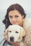 Young woman, dog labrador. Portrait of beautiful young woman playing with dog on the sea shore stock photography