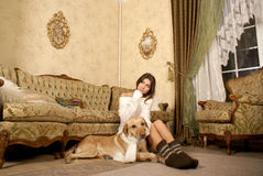 A young woman with a dog in a luxorious interior Royalty Free Stock Image