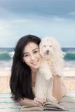 Young woman and dog lying at shore Stock Photo