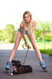 Young woman with dog on roller skates in the park Royalty Free Stock Photo