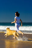 Young woman and dog running on the beach royalty free stock photo