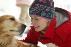 Young woman with dog in the snow. Young woman stroking labrador in the snow Royalty Free Stock Photos