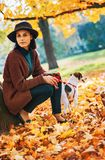 Young woman with dog standing outdoors in park in autumn Royalty Free Stock Image