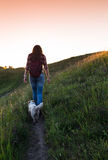 Young woman with dog on a sunny day hiking in high mountains Royalty Free Stock Photo