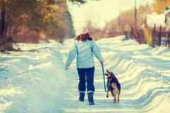 Young woman with dog walking on the snowy road royalty free stock photo