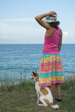 Young woman and dog watching the sea Royalty Free Stock Image