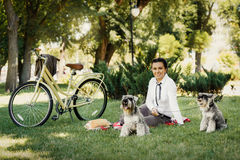 Young woman with dogs and bicycle having picnic in the park Royalty Free Stock Photo